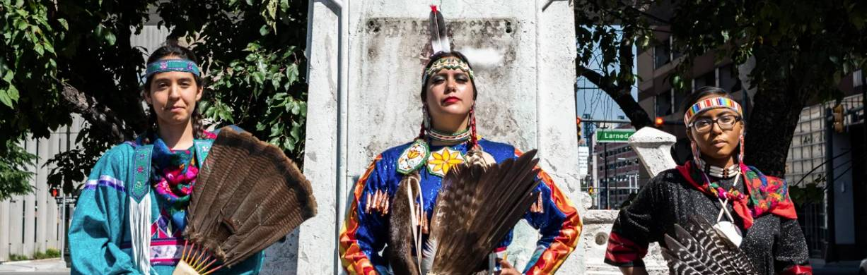 Three Indigenous women in traditional garb posing in front of site of removed Columbus statue